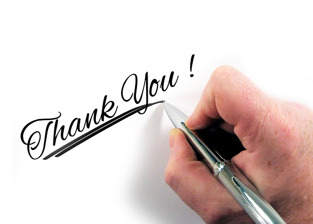 Person writing thank you on paper.